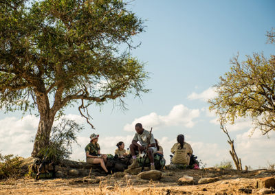 Tired from the uphill hike, trailists take a water break under a tree overlooking a waterhole. Zondi (male guide) keeps an eye out for approaching game